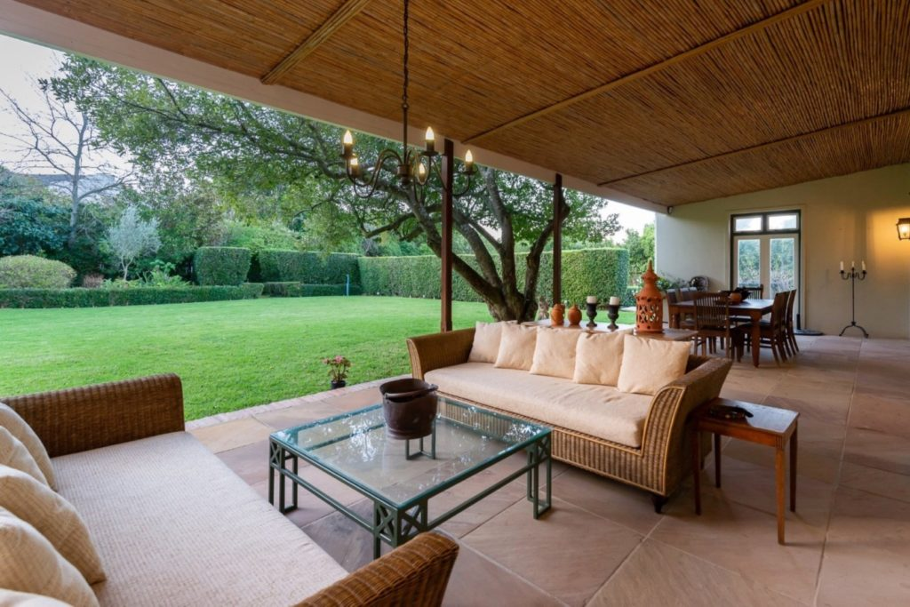 Outdoor sheltered area overlooks private garden and nature beyond